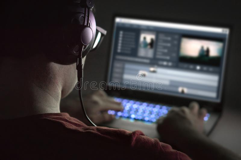 Video editing with laptop. Professional editor. Video editing with laptop. Professional editor adding special effects or color grading footage. Back view of stock images