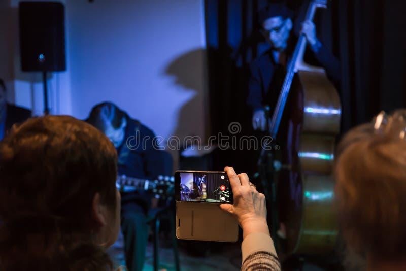 Video fucilazione con il vostro smartphone Contaminazione del concerto Musicisti che giocano il contrabbasso e la chitarra elettr fotografia stock