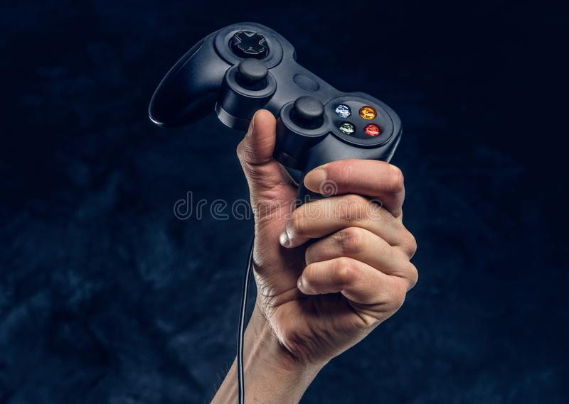 Video game console controller in gamer hand against the background of the dark wall. Video game console controller in gamer hand against a dark wall stock image