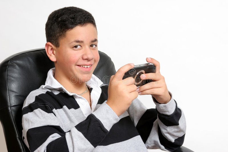 Video game happiness. A teenage boy happy to be playing his hand held video game stock photos