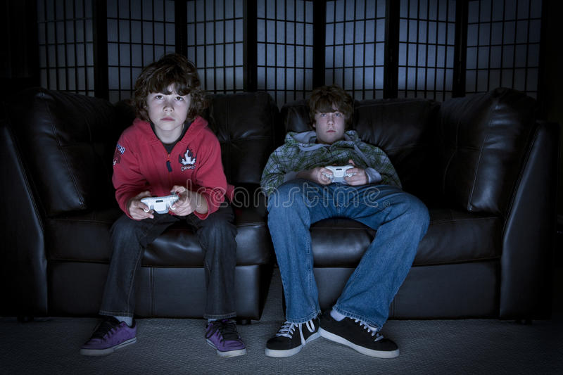 Video Games. Two boys sitting on a couch playing video games royalty free stock image