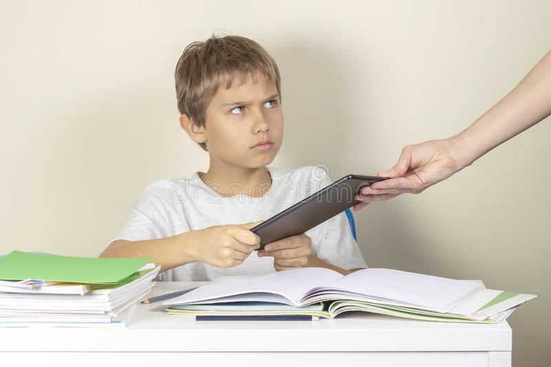 Video games addiction. Mother taking tablet away from the kid hands stock image