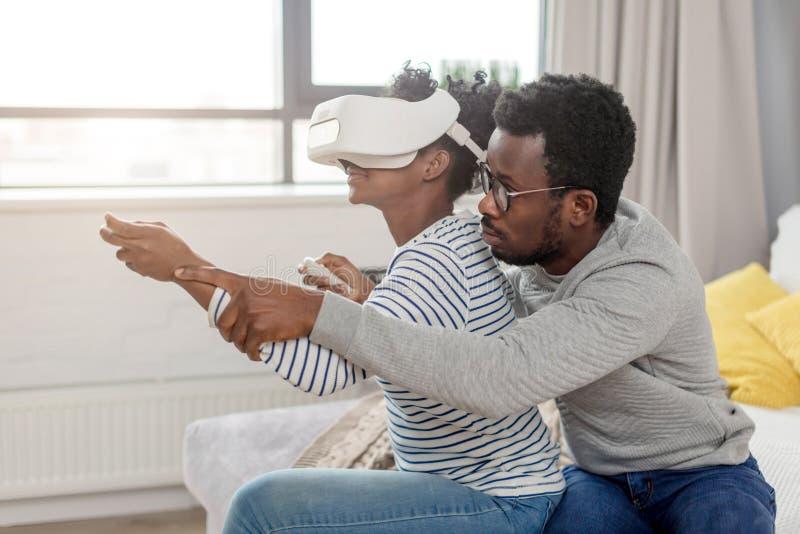 Video giochi africani del gioco delle coppie che indossano i vetri di realtà virtuale a casa fotografia stock libera da diritti