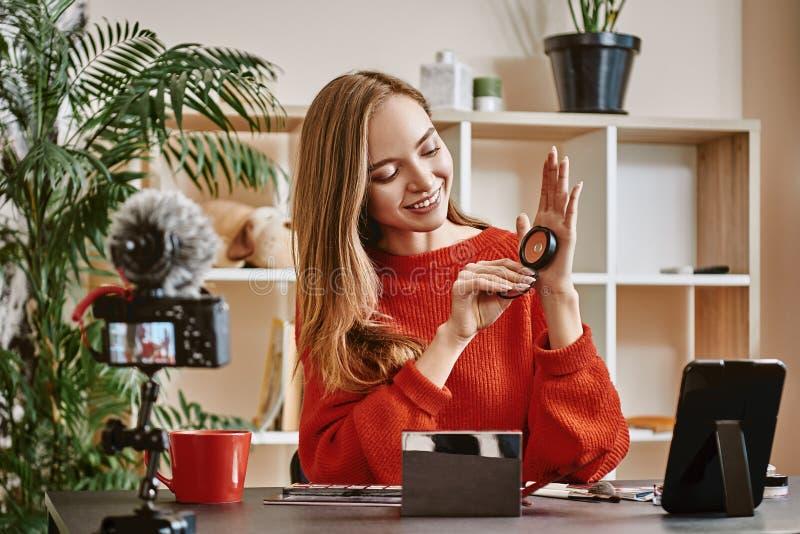 Video granskning Gullig och ung blogger som framlägger skönhetsprodukter, medan göra en ny video orubblig för hennes vlog royaltyfri foto