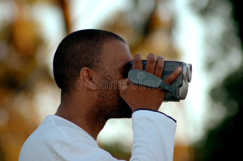 Video man. An African American man holding a video camera with his black hand and filming in nature to capture a moment in time forever royalty free stock image