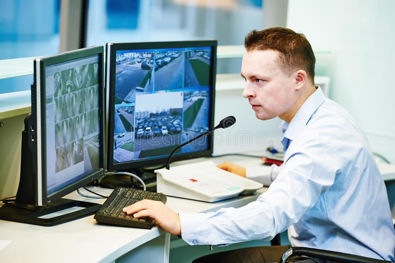 Video monitoring surveillance security system. Security guard officer watching video monitoring surveillance security system