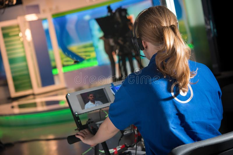 VIDEO OPERATOR GIRL REMOVES AS JOURNALIST TALKS INTERVIEW. IN TELEVISION STUDIO stock photos