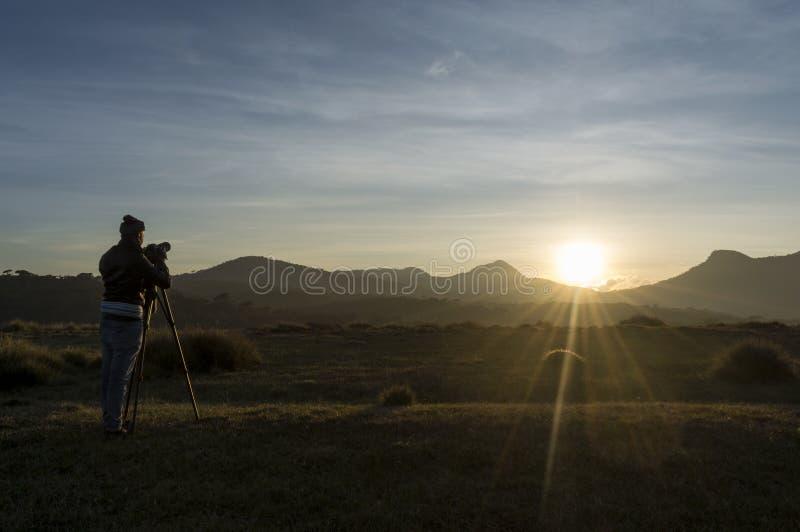 Video operatore nel corso della fabbricazione del tiro per il video documentario durante il tramonto fotografia stock libera da diritti