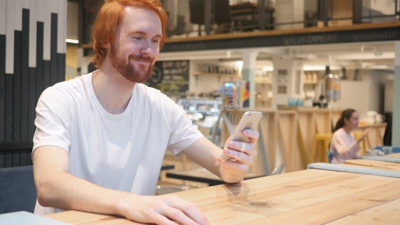 Video pratstund på Smartphone av mannen i kafé royaltyfri fotografi