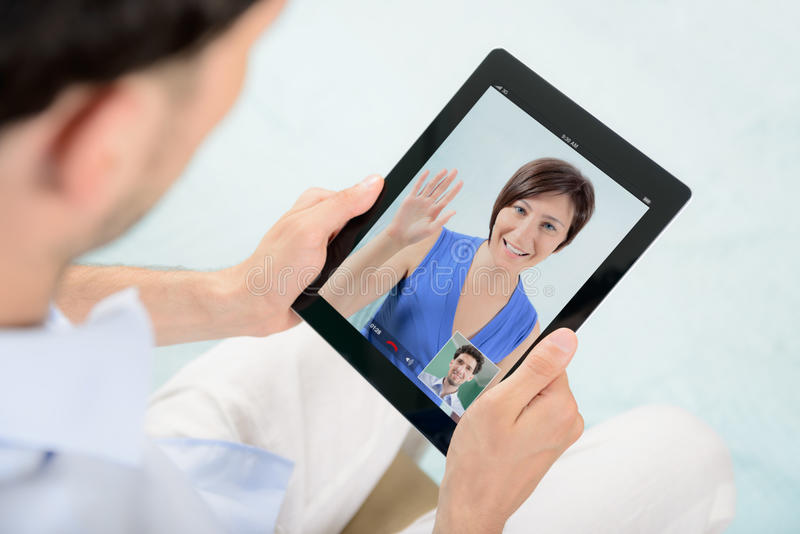 Video skype communication on apple ipad. A young couple talking to each other via online video chat