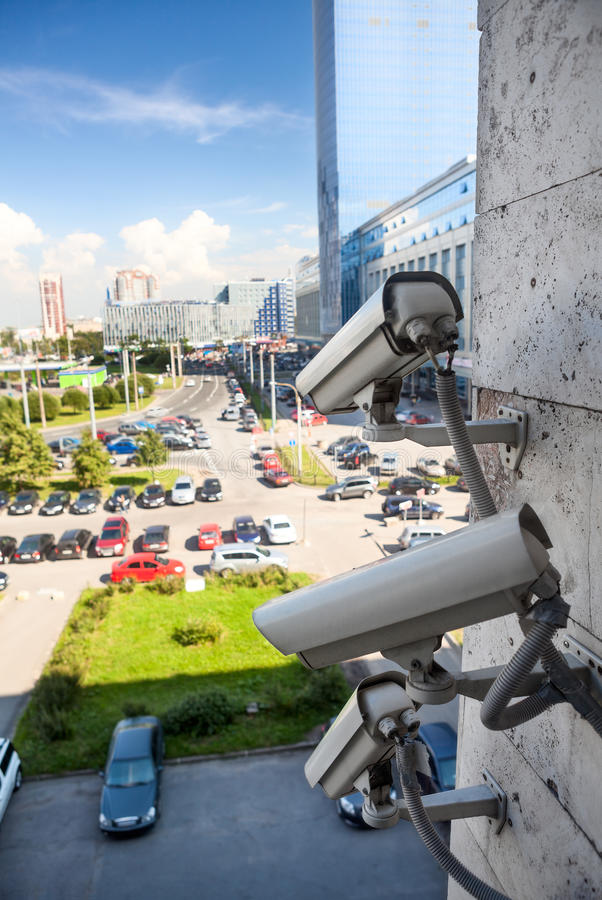 Video surveillance cameras. On building wall looking at street parking zone stock photos