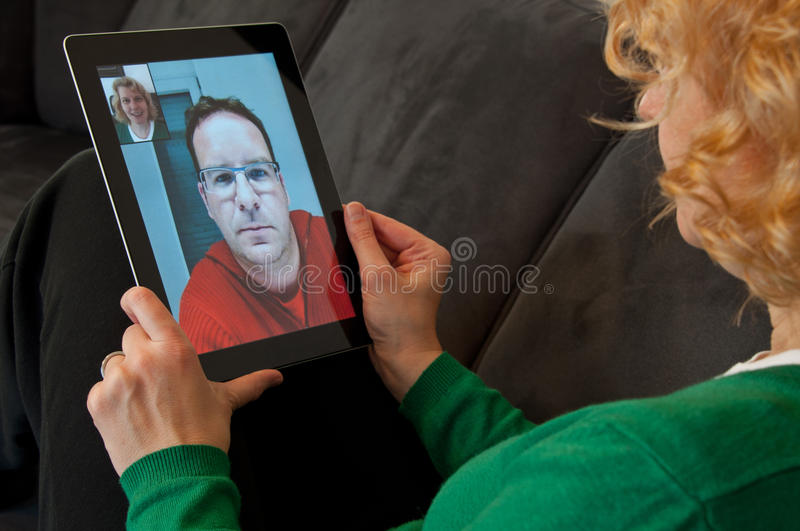 Video Telephony on Digital Tablet PC. Middle-aged women using video telephony on digital tablet pc royalty free stock photo