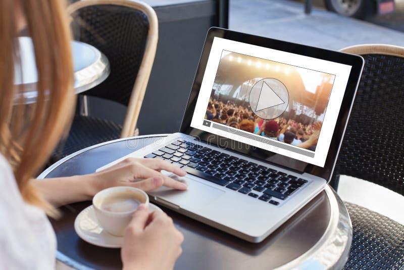 Video tryckning, online-konsert, kvinna som håller ögonen på gemet för levande musik på internet arkivfoto