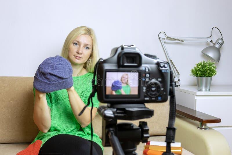 Video vlog o podcast femminile della registrazione di blogger, scorrente online Macchina fotografica vaga sul treppiede nella par immagini stock libere da diritti