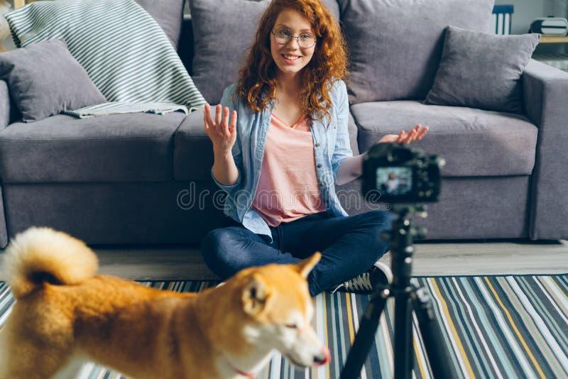 Videoblog di registrazione di blogger sveglio dell'adolescente che si siede sul pavimento a casa con il cane di animale domestico fotografia stock