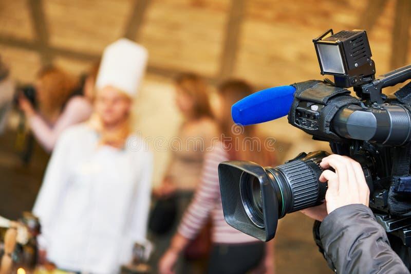 Videocamera di funzionamento del cineoperatore all'evento di notizie immagine stock libera da diritti