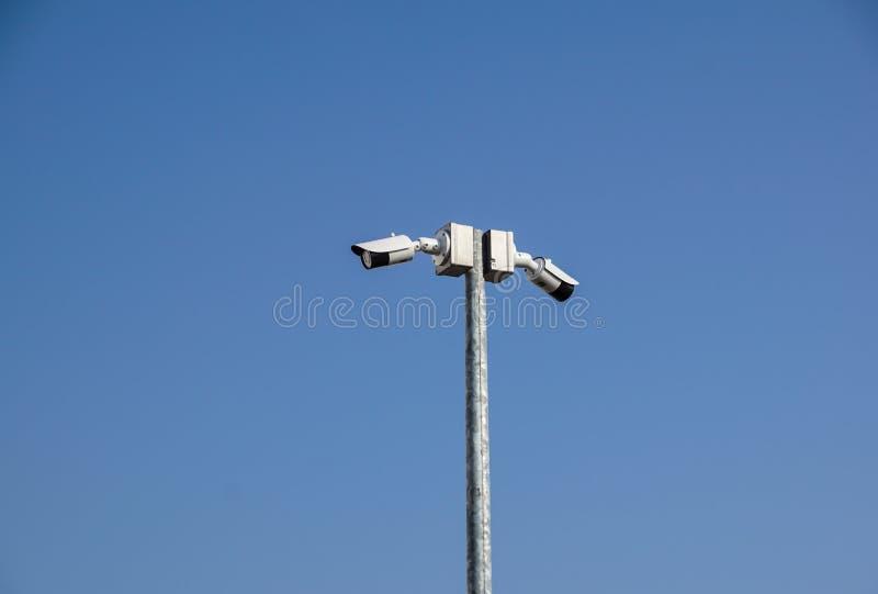Videocamera di sicurezza di sorveglianza del CCTV su un palo nero con il fondo del cielo blu fotografia stock libera da diritti