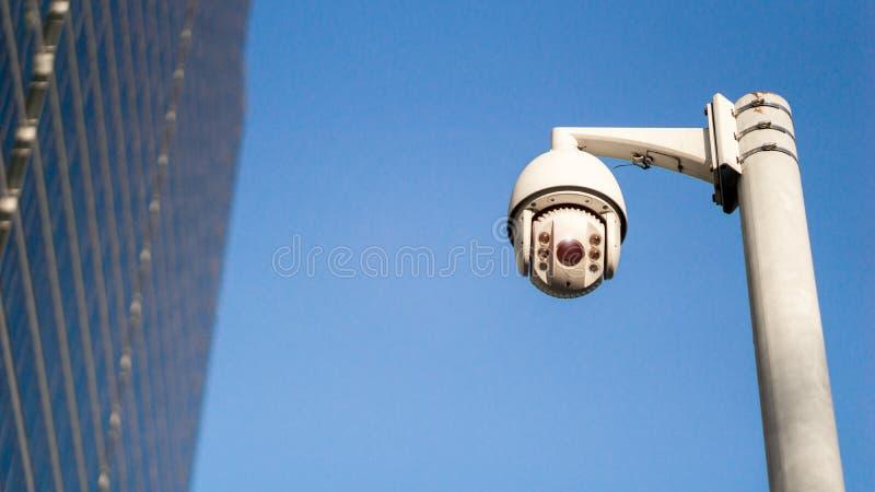 Videocamera di sicurezza di sorveglianza del CCTV sul palo in citt? con il fondo della costruzione della torre per controllo di a fotografia stock libera da diritti