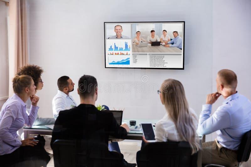 Videoconferência dos empresários na sala de reuniões imagens de stock royalty free