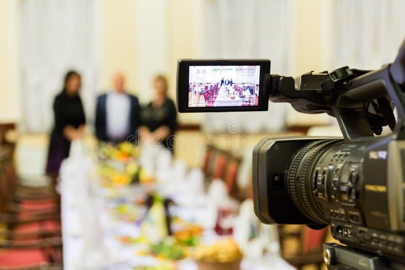 Videodreh an einem Restaurant an einem Bankett Kamerarecorder mit LCD-Anzeige Leute in der Halle stockbild