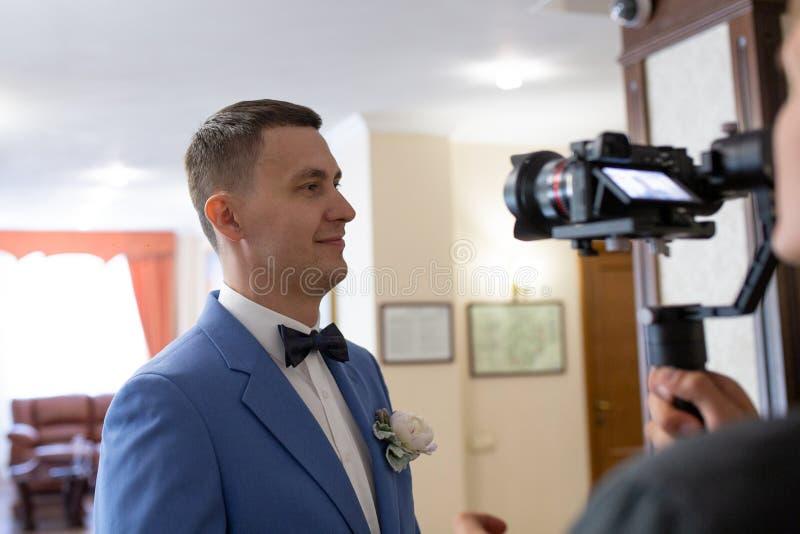 Videografie der Hochzeit mit dem Bräutigam in einem blauen Anzug mit Kamera, Bediener und Stabilisator lizenzfreies stockfoto