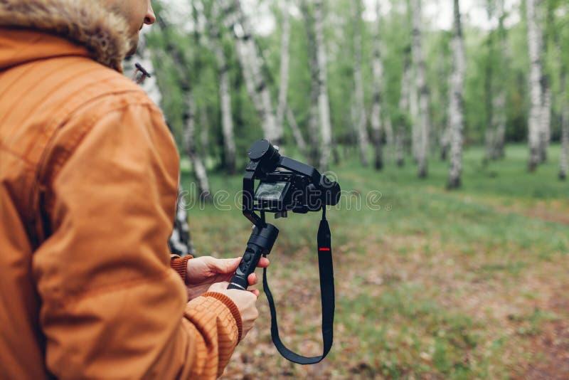 Videographer摄制春天使用做的steadicam和的照相机的森林人英尺长度 录影射击 免版税库存照片