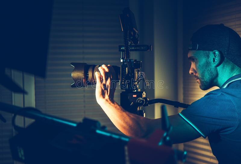 Videographer Camera Operator. Videography Industry. DSLR Cinema Video Camera Operator at Work. Taking Interior Shoots Using Artificial Lighting royalty free stock photos