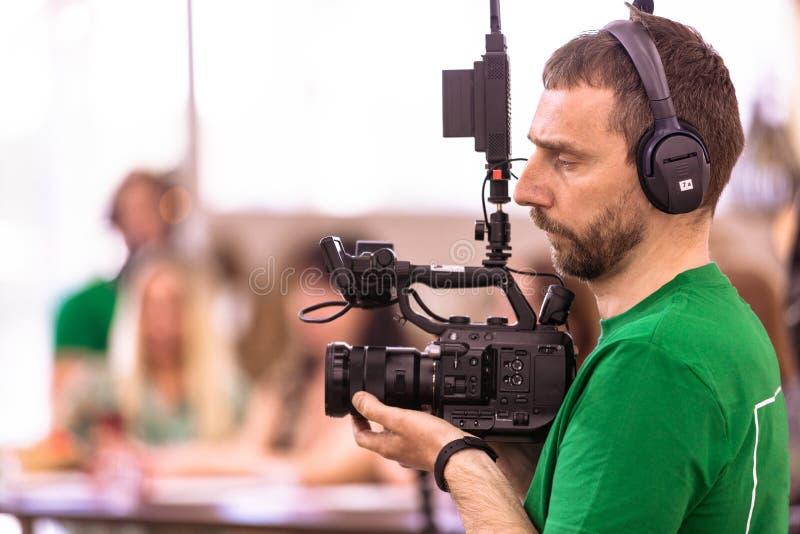 Videographer, das einen Film oder eine Fernsehsendung in einem Studio mit einer Berufskamera, B?hne hinter dem Vorhang schie?t stockbilder