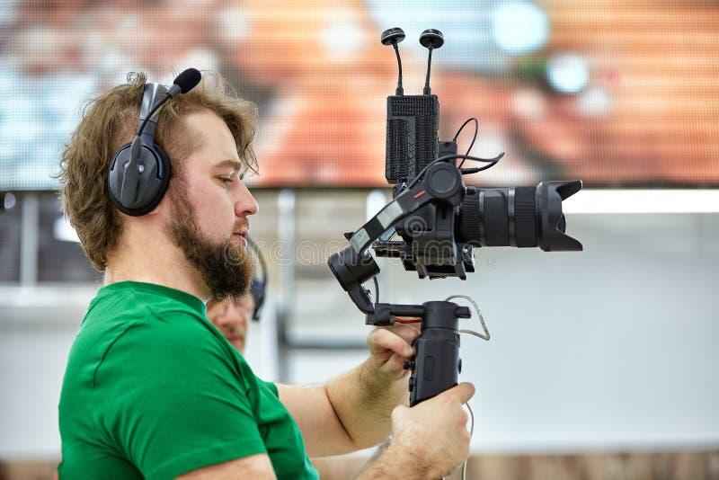 Videographer, das einen Film oder eine Fernsehsendung in einem Studio mit einer Berufskamera, B?hne hinter dem Vorhang schie?t stockfoto