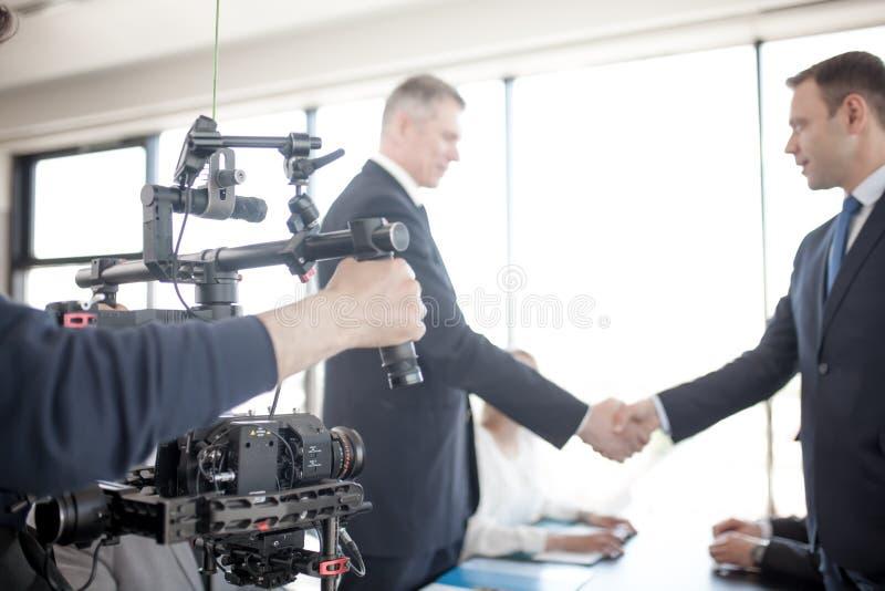 Videographer, das Video von den Geschäftsleuten herstellt stockfoto