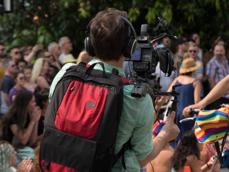 Videographer die de openlucht van de de gebeurtenisvideocamera van de filmmenigte installatie mic werken stock foto's