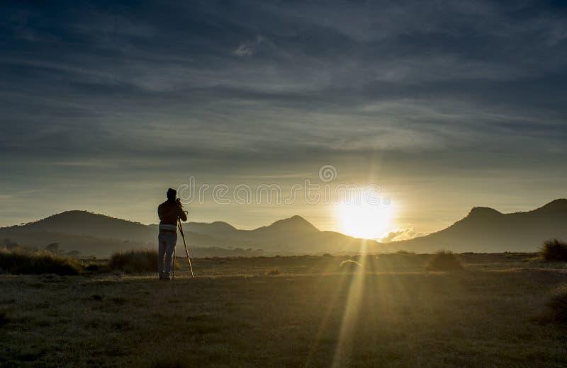 Videographer en curso de fabricación del lanzamiento para el vídeo documental durante puesta del sol fotografía de archivo