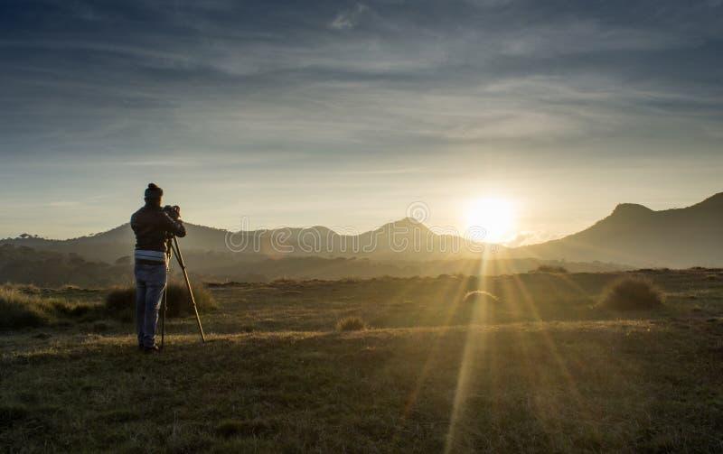 Videographer en curso de fabricación del lanzamiento para el vídeo documental durante tiempo de la puesta del sol foto de archivo