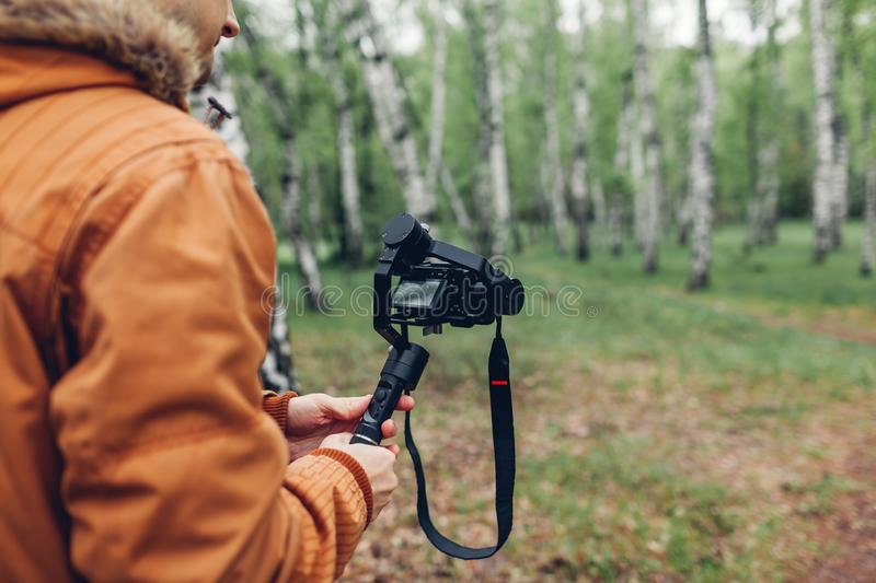 Videographer filming spring forest. Man using steadicam and camera to make footage. Video shoot. Digital devices for video shoot royalty free stock photo