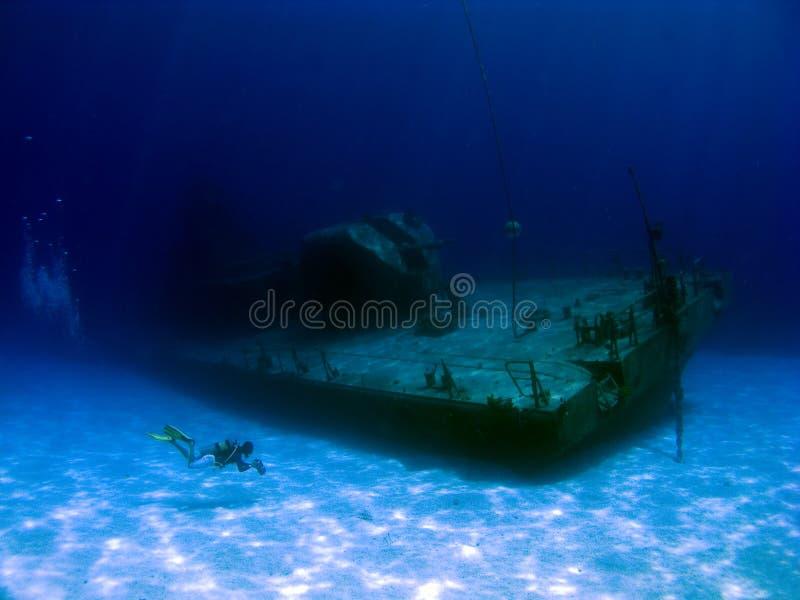 Videographer filming a sunken Shipwreck. Videographer filming the sunken Shipwreck Tibbits in Cayman Brac royalty free stock photos