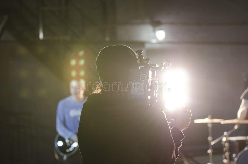 Videographer profissional usando a câmara de vídeo digital do cinema para filmar uma vídeo clip imagem de stock royalty free