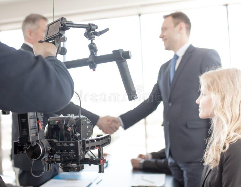 Videographer que hace el vídeo de hombres de negocios imagen de archivo libre de regalías