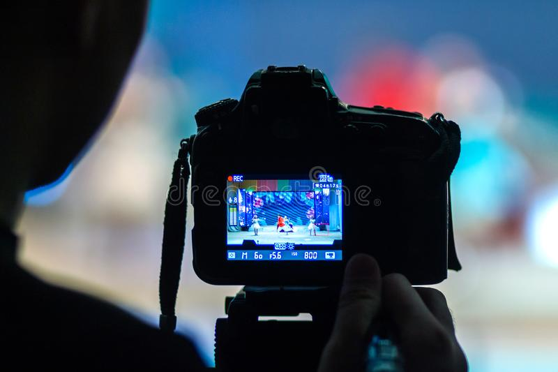 The videographer records some kind of abstract New Year`s performance of artists on stage with the help of the DSLR camera. Blurr royalty free stock photography
