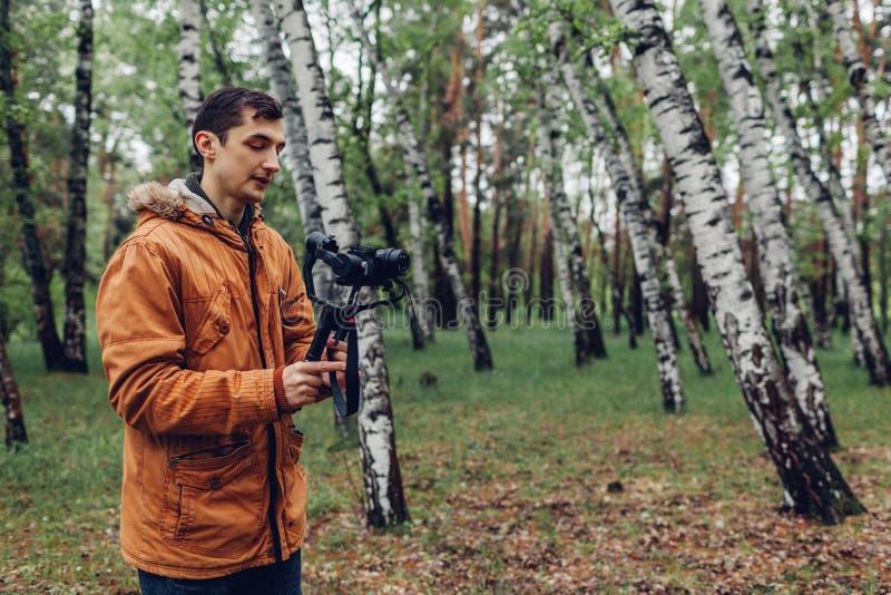 Videographer-Schmierfilmbildungsfr?hlings-Waldmann unter Verwendung des steadicam und Kamera, zum von Gesamtl?nge herzustellen Vi lizenzfreies stockbild