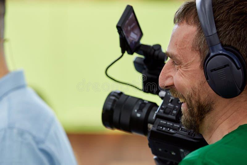 Videographer som skjuter en film eller en tv-program i en studio med en yrkesm?ssig kamera, i kulisserna royaltyfri fotografi
