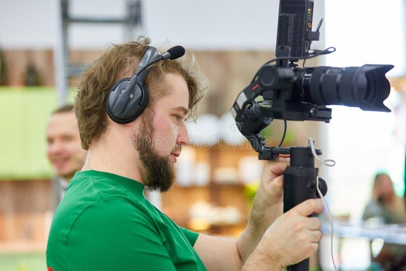 Videographer som skjuter en film eller en tv-program i en studio med en yrkesm?ssig kamera, i kulisserna arkivbilder