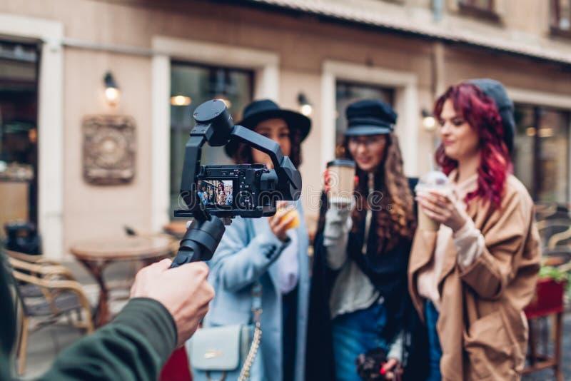 Videographer在城市街道上的摄制模型 使用做的steadicam和的照相机的人英尺长度 录影射击 免版税库存图片