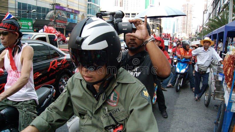 Videographer sur la démonstration rouge de chemise photo libre de droits