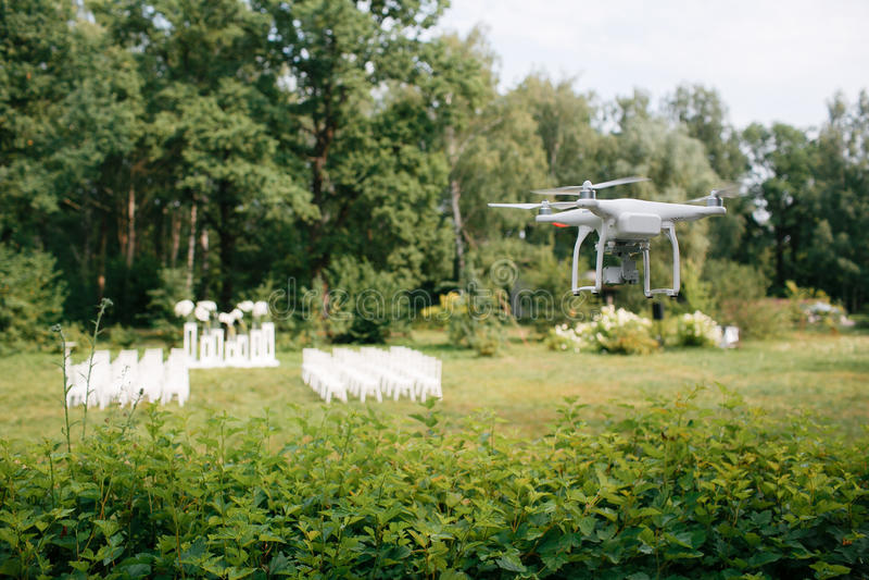 Videographybröllopceremoni från luften en liten spionkvadrathelikopter spanar surrflyg till och med träden i skog arkivbild