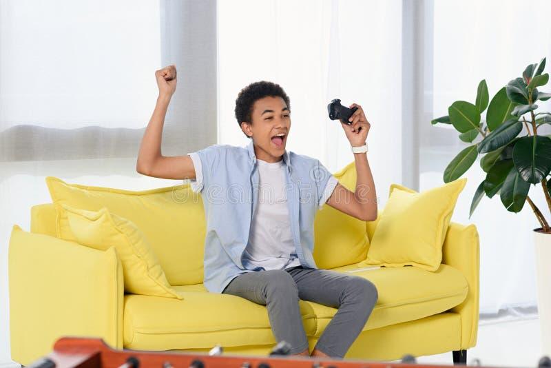 videojuego que gana del adolescente afroamericano feliz y mostrar gesto del sí foto de archivo libre de regalías