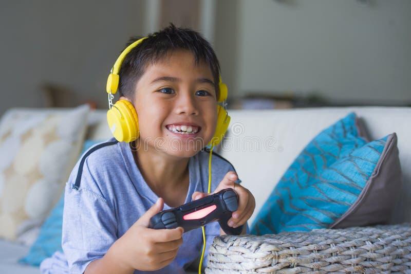 Videojuego que juega del niño latino en línea emocionado y feliz con los auriculares que detienen al regulador que goza divirtién imágenes de archivo libres de regalías
