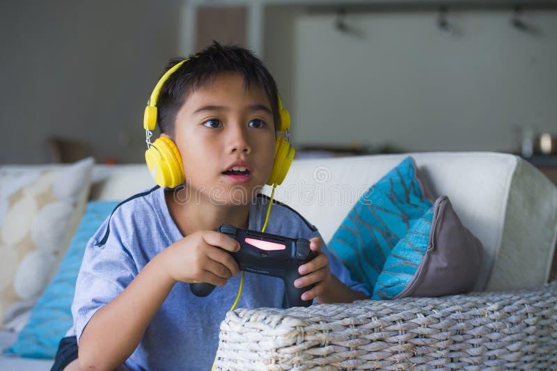 Videojuego que juega del pequeño niño latino joven en línea emocionado y feliz con los auriculares que sostienen el regulador que imágenes de archivo libres de regalías