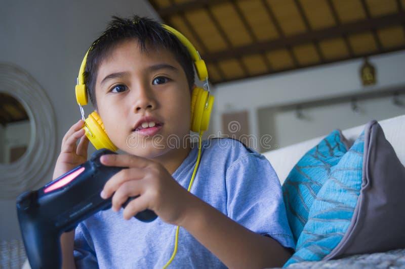 Videojuego que juega del pequeño niño latino joven en línea emocionado y feliz con los auriculares que sostienen el regulador que imagen de archivo