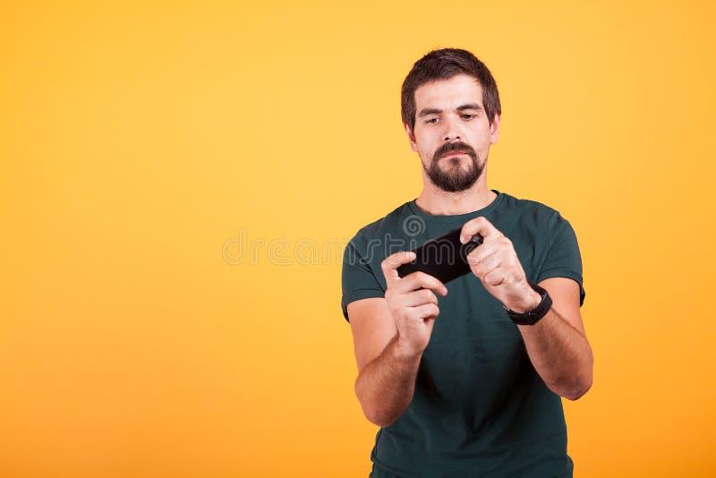 Videojugador adulto que juega a los videojuegos en su smartphone imagenes de archivo