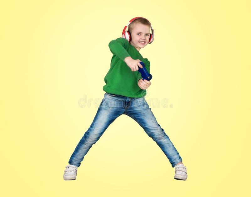 Videojugador del muchacho en auriculares con la palanca de mando que juega al juego de ordenador Aislado en fondo amarillo imagen de archivo libre de regalías